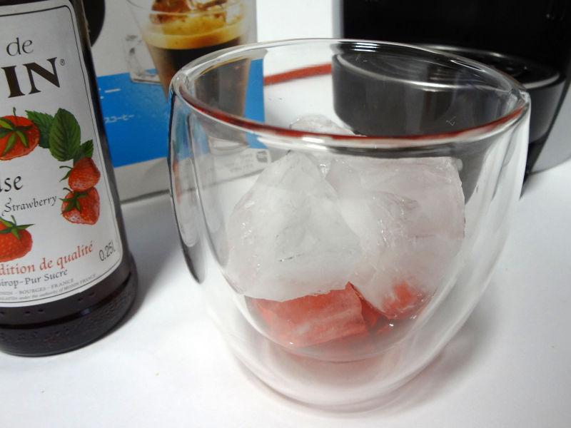 ストロベリーシロップと氷が入ったグラス